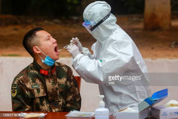 This photo taken on February 11 2020 shows medical staff members collecting samples from Chinese paramilitary police officers to be tested for the...