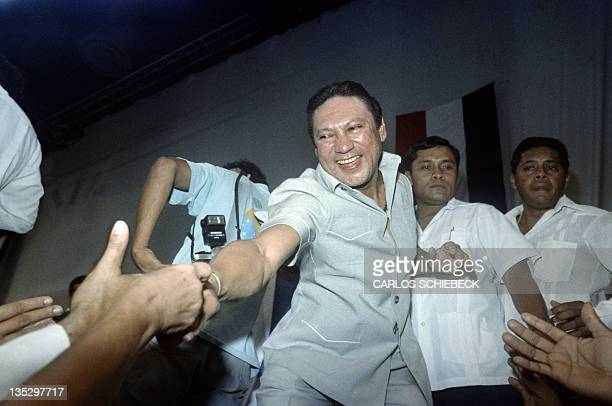 This photo taken on February 12 1988 in Panama City shows General Manuel Antonio Noriega reaching down to shake hands of followers who attended...