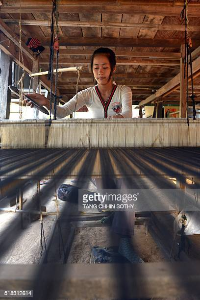 This photo taken on February 12 2013 shows a young Cambodian woman weaving with silk at her home on Koh Dach island near Phnom Penh AFP PHOTO / TANG...