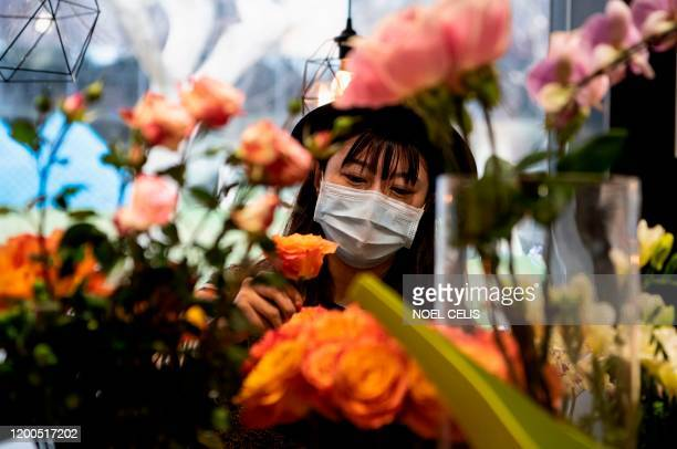 This photo taken on February 12 2020 shows florist Zhao Yuanyuan wearing a protective face mask as she arranges flowers in her shop in Shanghai ahead...