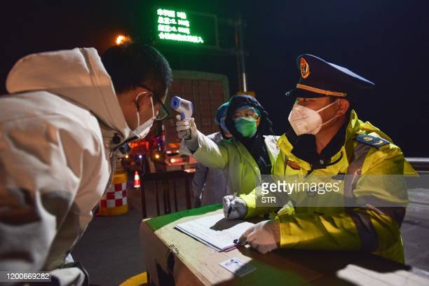 This photo taken on February 13, 2020 shows a staff member checking temperature of a driver at an exit of a highway in Zhangjiakou in China's...