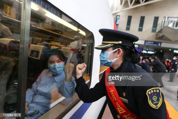 This photo taken on February 13, 2020 shows a train attendant gesturing to medical staff leaving for Wuhan in Nanchang, China's central Jiangxi...
