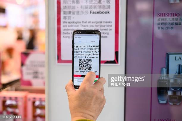 This photo taken on February 13, 2020 shows muscular atrophy patient Steven Yan scanning a barcode with his mobile phone to receive updates on face...