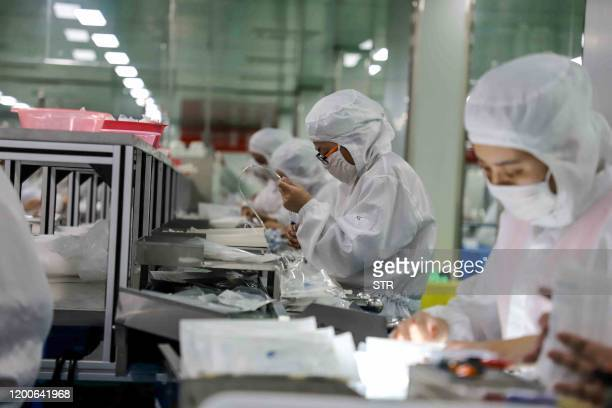 This photo taken on February 13 2020 shows workers producing medical supplies at a factory in Binzhou in China's eastern Shandong province The death...