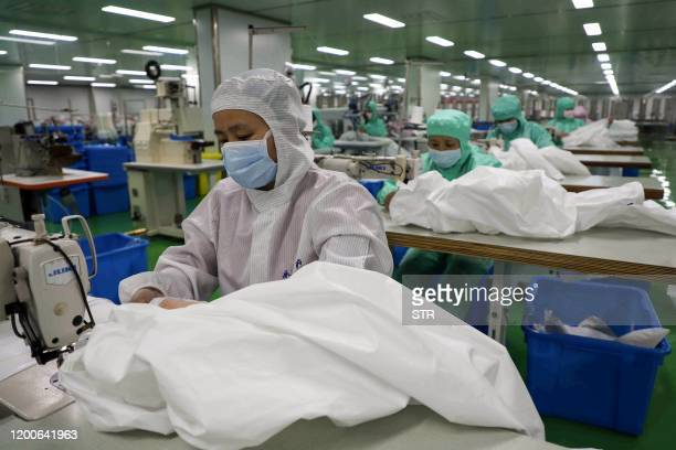 This photo taken on February 13 2020 shows workers producing protective suits at a factory in Binzhou in China's eastern Shandong province The death...