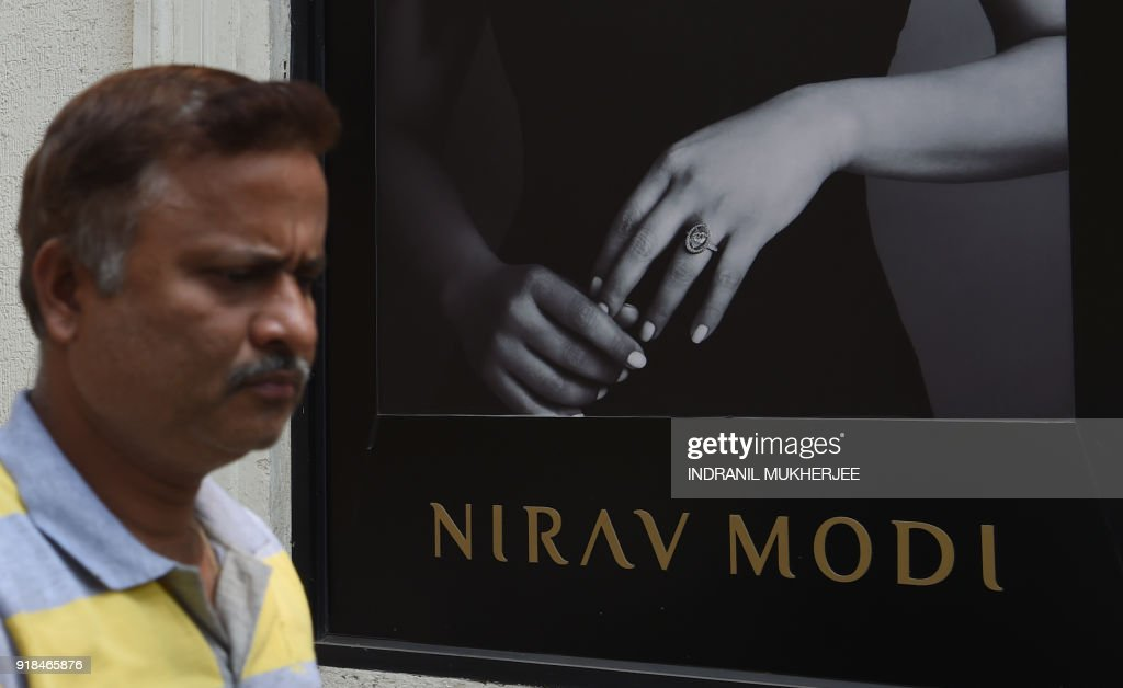 This photo taken on February 14 2018 shows an Indian man walking past a branch of the luxury jewellery store Nirav Modi in Mumbai Indian...