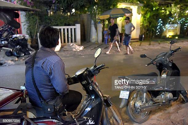 This photo taken on February 16 2016 shows a Cambodian civilian investigator from Action Pour Les Enfants watching tourists walk along a popular bar...