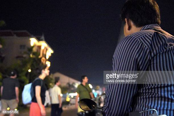 This photo taken on February 16 2016 shows a Cambodian civilian investigator from Action Pour Les Enfants watching tourists walk on a street in Siem...