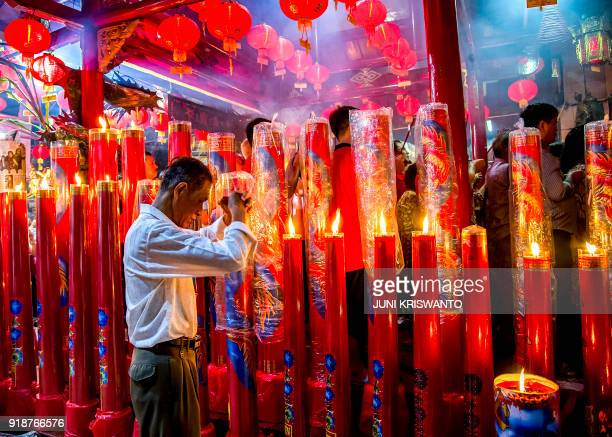This photo taken on February 16 2018 shows a ChineseIndonesian man praying on the eve of the Lunar New Year in Surabaya East Java province...