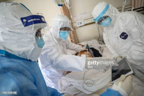 This photo taken on February 16, 2020 shows a doctor looking at an image as he checks a patient who is infected by the COVID-19 coronavirus at the...
