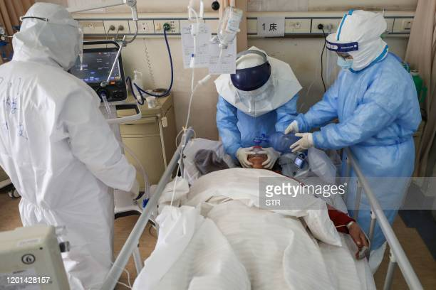 This photo taken on February 16, 2020 shows medical staff members treating a patient infected by the COVID-19 coronavirus at the Wuhan Red Cross...
