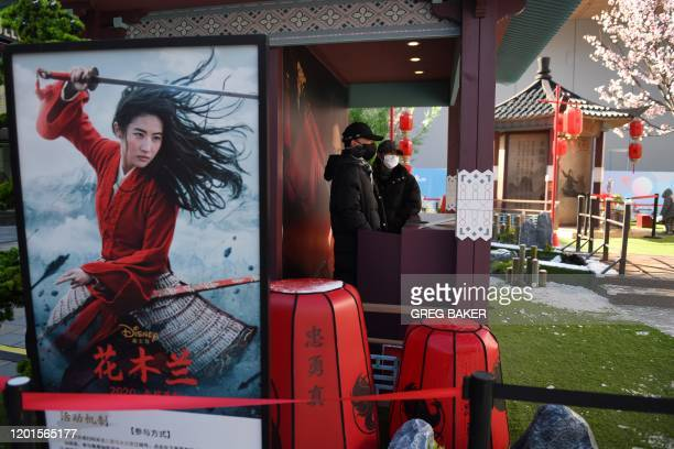 "This photo taken on February 16, 2020 shows two workers wearing face masks manning a promotional stand for the Disney move ""Mulan"" in an almost empty..."