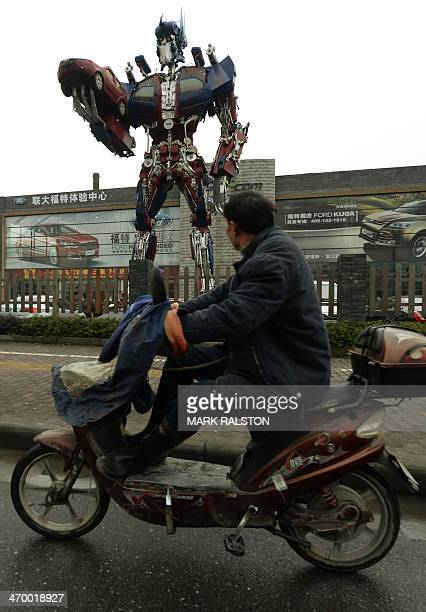 This photo taken on February 17 2014 shows a man riding past a transformer robot advertising a Ford car dealership in Hangzhou Zhejiang Province Ford...