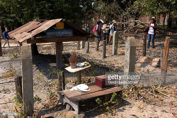 This photo taken on February 17 2016 shows Cambodian students looking at former Khmer Rouge leader Pol Pot's grave in the Anlong Veng district in...