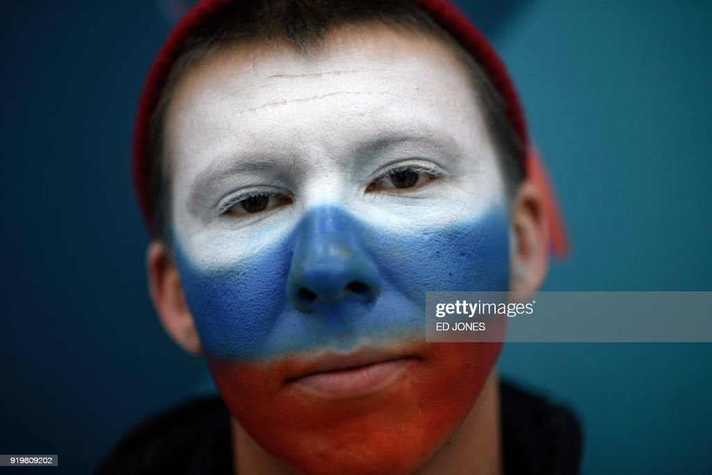 TOPSHOT - This photo taken on February 17, 2018 shows a Russia fan posing for a photo before the men's preliminary round ice hockey match between the US and Olympic Athletes from Russia during the Pyeongchang 2018 Winter Olympic Games at the Gangneung Hockey Centre in Gangneung. / AFP PHOTO / Ed JONES