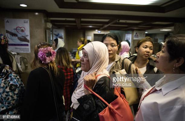 This photo taken on February 17 2018 shows Filipina workers from Kuwait at the Overseas Workers Welfare Administration building after arriving at...