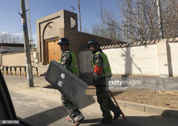 This photo taken on February 17 2018 shows local police patroling a village in Hotan prefecture in China's western Xinjiang region The predominantly...