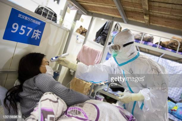 This photo taken on February 17 2020 shows a member of the medical staff checking the body temperature of a patient who has displayed mild symptoms...