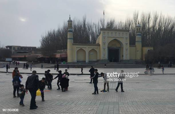 This photo taken on February 18 2018 shows children playing outside the Idkah mosque in Kashgar in China's western Xinjiang region The predominantly...