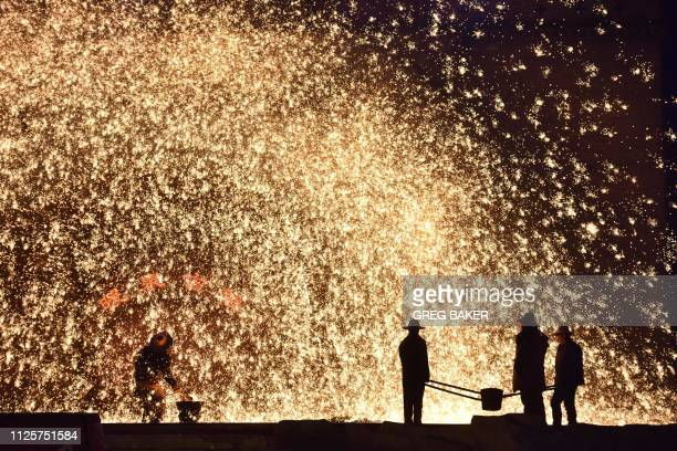 TOPSHOT This photo taken on February 18 2019 shows a Chinese blacksmith throwing molten metal against a cold stone wall to create a shower of sparks...