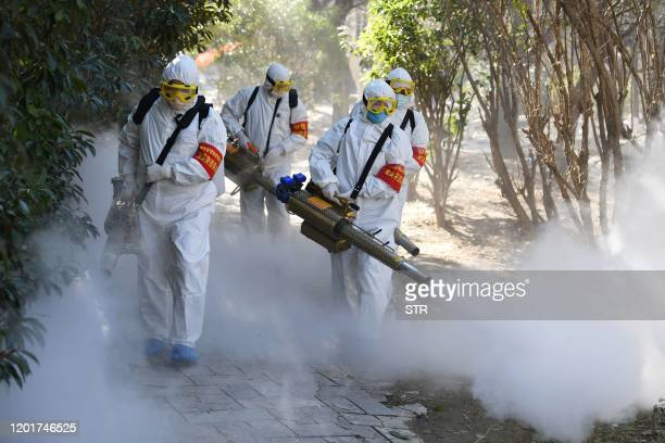 This photo taken on February 18, 2020 shows members of a police sanitation team spraying disinfectant as a preventive measure against the spread of...