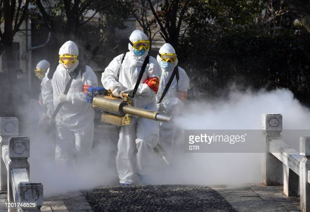 This photo taken on February 18, 2020 shows members of a police sanitation team spraying disinfectant on a bridge as a preventive measure agaist the...
