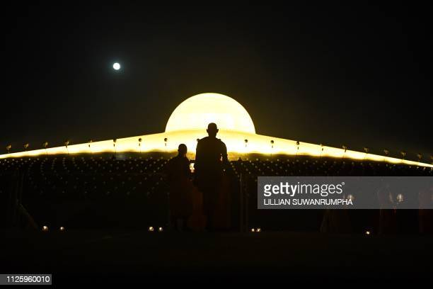 This photo taken on February 19 2019 shows Buddhist monks carrying lit candles while the full moon rises during prayers to mark Makha Bucha Day at...