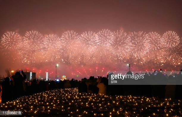 This photo taken on February 19 2019 shows people watching a fireworks display during the Lantern Festival which marks the end of Lunar New Year...