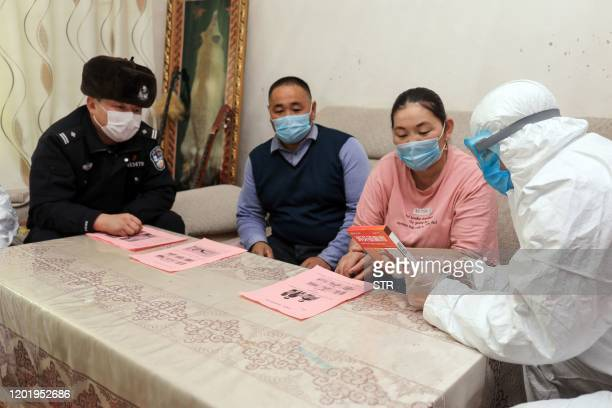 This photo taken on February 19, 2020 shows police officers visiting residents who live in remote areas in Altay, farwest China's Xinjiang region, to...
