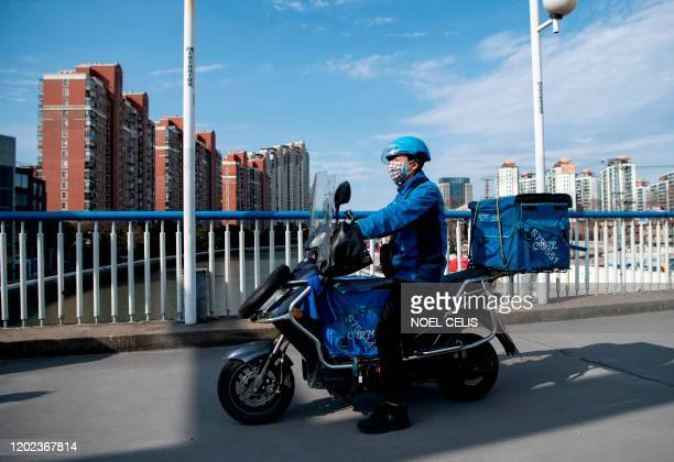 This photo taken on February 19 motorcycle delivery worker Gao Yuchao driving on an overpass to deliver goods ordered online along a street in...