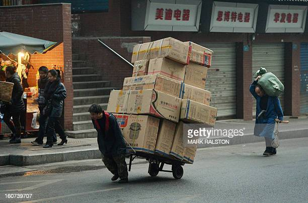 This photo taken on February 2 2013 shows a Chinese worker pulling a large load of boxes in the Jiafeng Bei shopping area in Chongqing Chinese state...