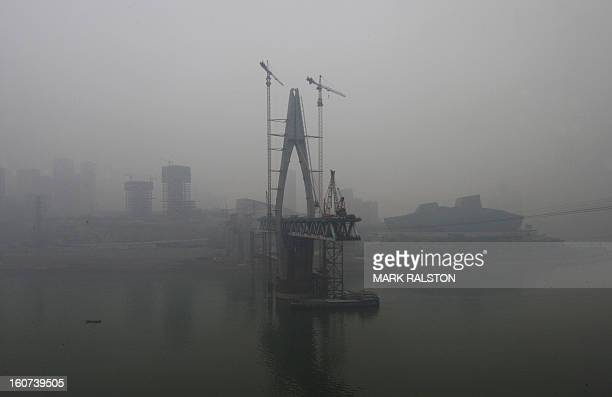 This photo taken on February 2 2013 shows the new Qianximen Bridge and the Grand Theatre from across the Jialing River in Chongqing Chinese state...
