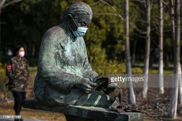 This photo taken on February 2, 2020 shows sculptures wearing protective facemasks at a park in Huaian in China's eastern Jiangsu province, amid a...