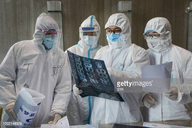 This photo taken on February 20 2020 shows doctors looking at a lung CT image at a hospital in Yunmeng county Xiaogan city in China's central Hubei...
