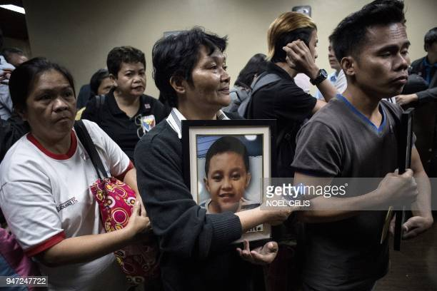 This photo taken on February 21 2018 shows Melinda Colite holding a picture of her grandson Zandro Colite who she says died after getting injected...