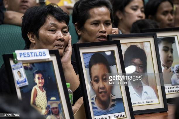 This photo taken on February 21 2018 shows Melinda Colite with a picture of her grandson Zandro Colite who she says died after getting injected with...