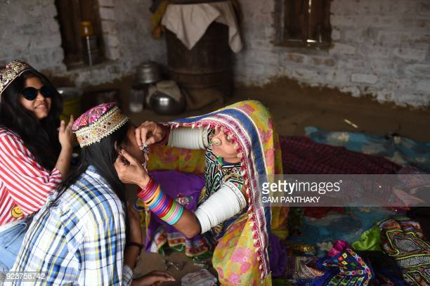 This photo taken on February 22 2018 shows an Indian artist making traditional Banni embroidery for a tourist at a workshop at Hodka village in the...