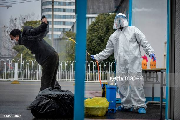 This photo taken on February 22, 2020 shows a man who has recovered from the COVID-19 coronavirus infection being disinfected by a medical staff...