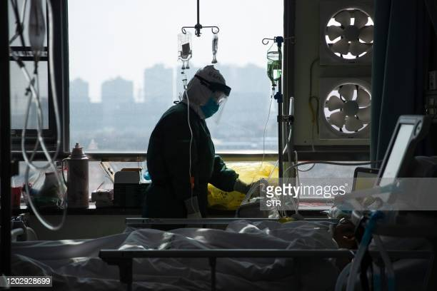 This photo taken on February 22, 2020 shows a medical staff member treating a patient infected by the COVID-19 coronavirus at a hospital in Wuhan in...