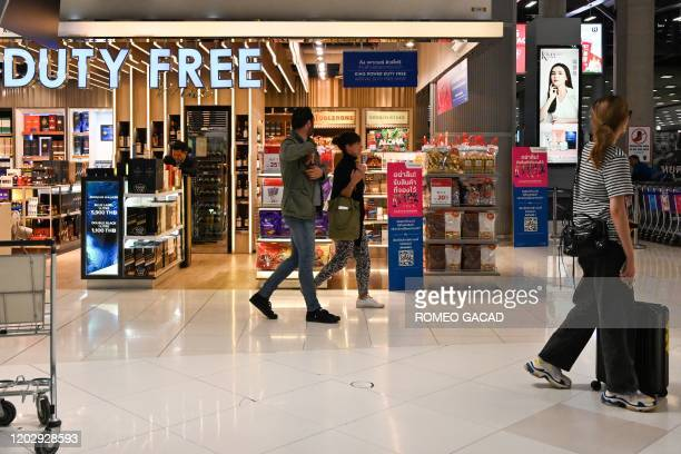 This photo taken on February 23, 2020 shows passengers walking past a duty free shop at the arrival area of Suvarnabhumi Airport in Bangkok.