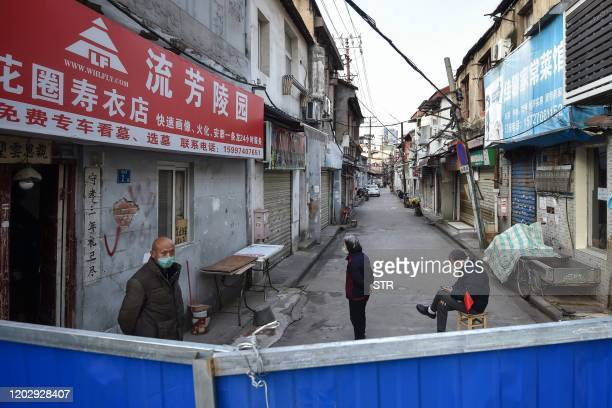 This photo taken on February 23, 2020 shows people standing on a street by a barrier to stop others from entering, in Wuhan in China's central Hubei...