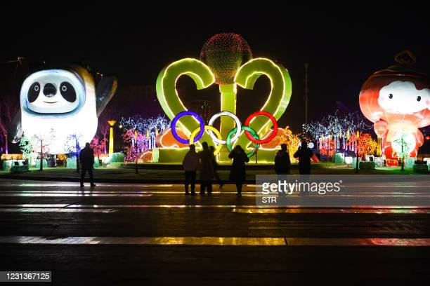 This photo taken on February 24, 2021 shows people visiting a lantern show on the theme of 2022 Beijing Winter Olympic and Paralympic Games at the...