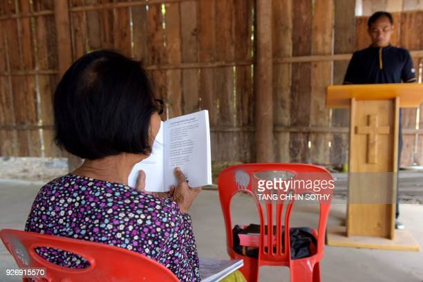 This photo taken on February 25 2018 shows former Khmer Rouge cadre Im Chaem reading a Bible at a makeshift church next to her house in Anlong Veng...