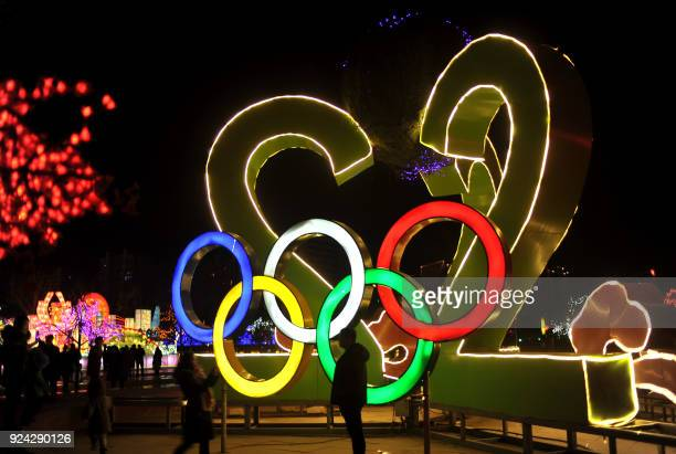 TOPSHOT This photo taken on February 25 2018 shows people looking at a lantern with the Olympic rings at a lantern show in Zhangjiakou in China's...
