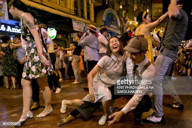 This photo taken on February 25 2018 shows people swing dancing in front of Phra Pathom Chedi temple in the central Thai province of Nakhon Pathom...