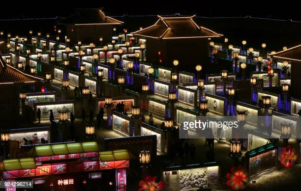 This photo taken on February 25 2018 shows people visiting a lantern show in Zhangye in China's northwestern Gansu province as the Lunar New Year...