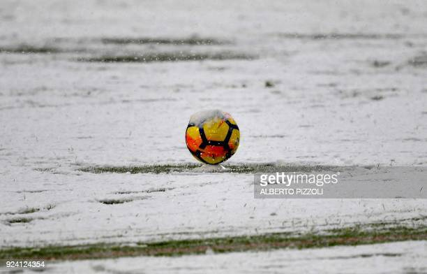 This photo taken on February 25 2018 shows snow covering a ball and the pitch prior to the postponement of the Italian Serie A football match...