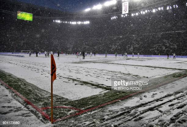 TOPSHOT This photo taken on February 25 2018 shows snow covering the pitch prior to the postponing of the Italian Serie A football match Juventus...