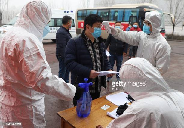 This photo taken on February 25 2020 shows a migrant worker having his temperature taken after arriving on a chartered pointtopoint bus from Henan at...