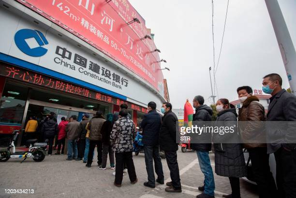 This photo taken on February 25, 2020 shows customers lining up to have their temperature taken before entering the bank in Nantong, in China's...